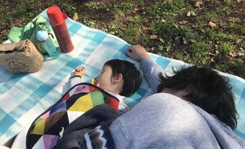 レジャーシートに寝転ぶ親子